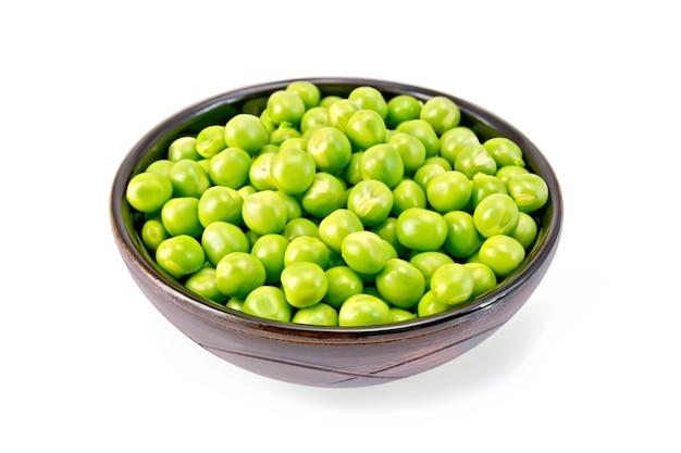 Зеленый горошек в коричневой миске, изолированные на белом фоне Premium Фотографии