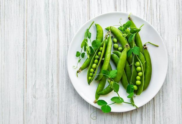 흰색 나무 표면에 접시에 녹색 완두콩