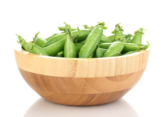 Зеленый горошек в деревянной миске на белом