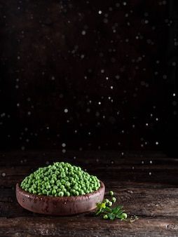 Green peas in a plate on dark