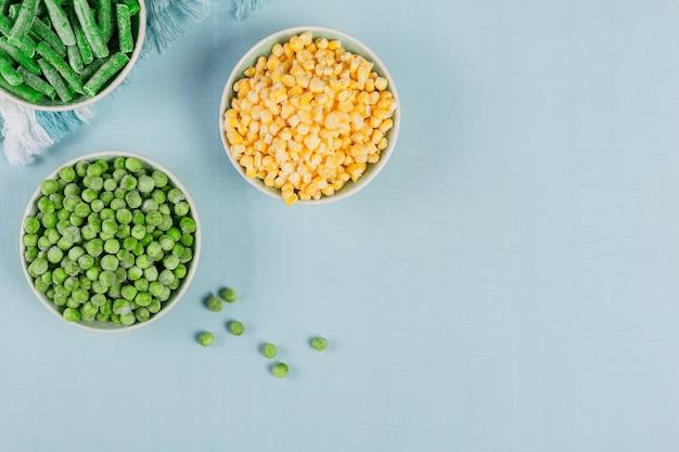 グリーンピース、スイートコーン、カットしたインゲンをボウルに入れます。速い料理のための自家製の準備の概念。健康的なベジタリアン料理のコンセプト