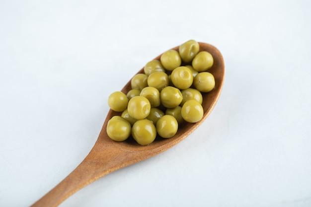 Piselli verdi su cucchiaio di legno