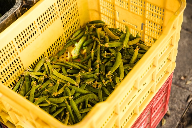 Green peas in yellow plastic crate at market
