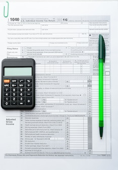 Green pen and calculator on tax form