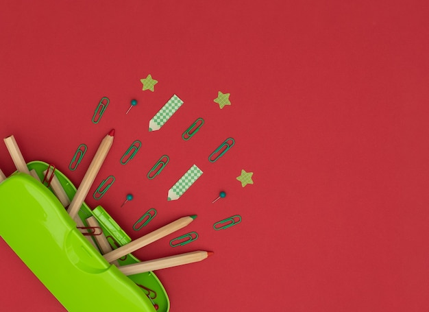Green pencil case, wooden pencils, red and green clips and pins, pencil and star shaped paper stickers on red.