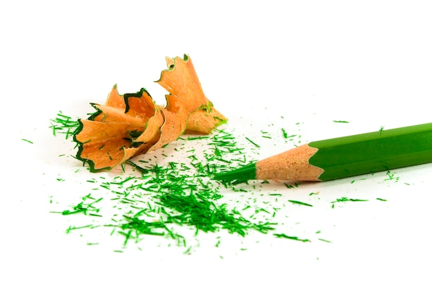 Green pencil and sawdust on white background