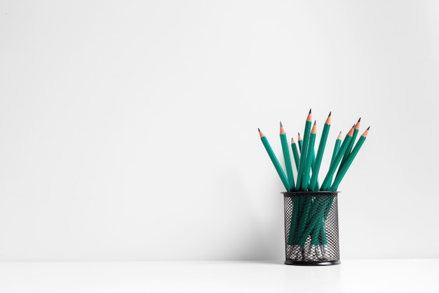 Green pencils in a holder, school supplies on white background
