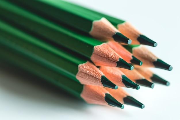 白い背景の上の緑の鉛筆。オフィス、図面。