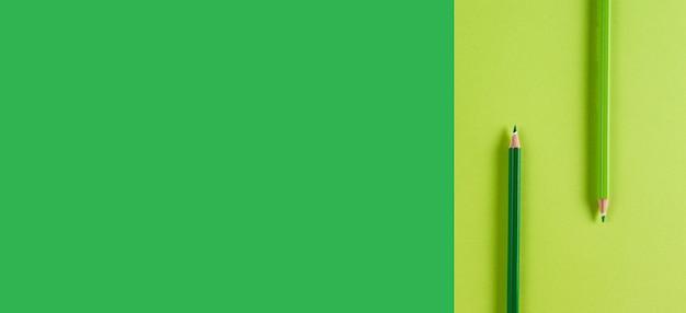 パステルグリーンのコントラストの背景に緑の鉛筆最小限の創造的な概念