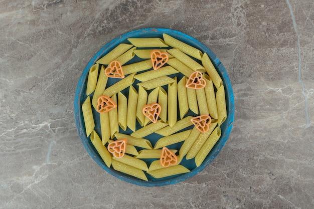 Зеленое пенне и макаронные изделия в форме сердца на синей тарелке.