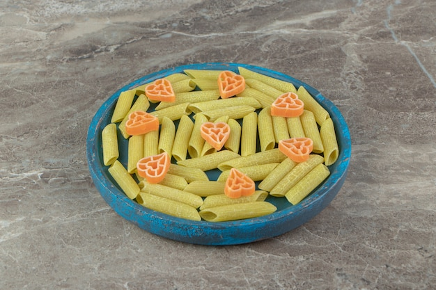 Penne verdi e pasta a forma di cuore su piatto blu