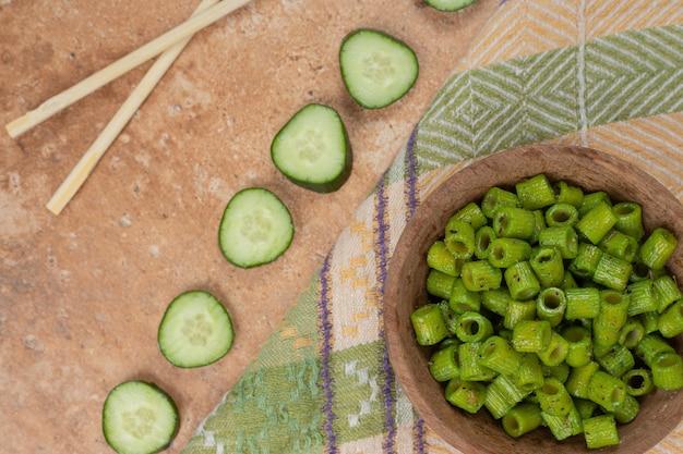 テーブルクロスにグリーンのペンネパスタとキュウリのスライス。高品質の写真