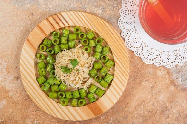 Зеленые макароны пенне и вермишель на деревянной тарелке со стаканом сока.