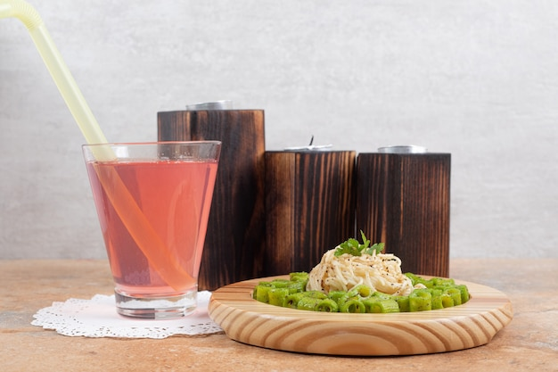 Green penne pasta and vermicelli on wooden plate with glass of juice
