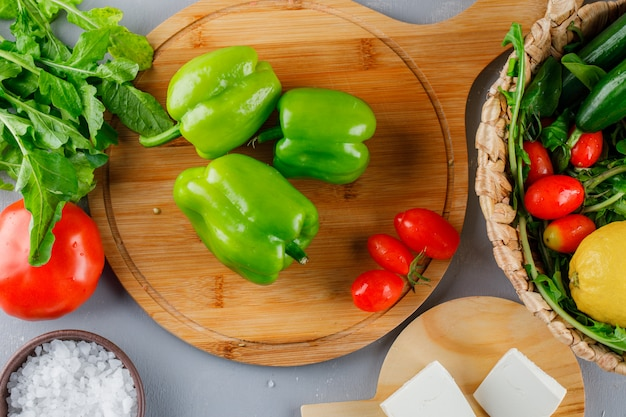 Green pepper on a cutting board with tomatoes, salt, cheese, lemon top view on a gray surface