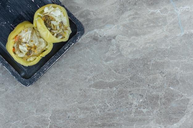 Peperone verde ripieno di crauti su piatto di legno nero.