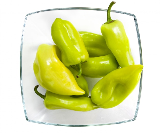 Green peppers in a glass vase on white