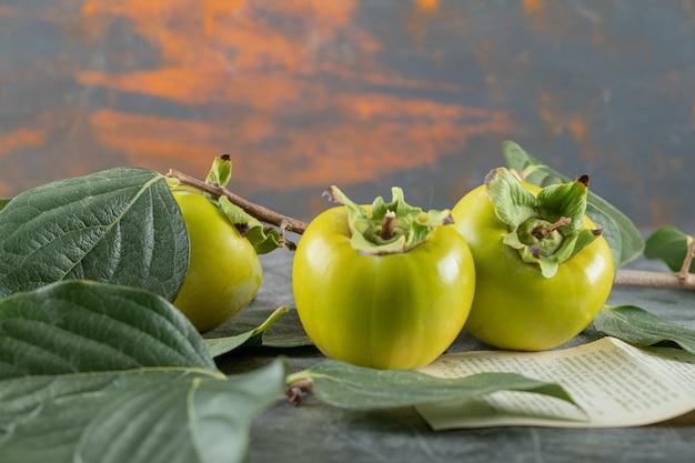 葉と大理石のテーブルの本のページと緑の柿