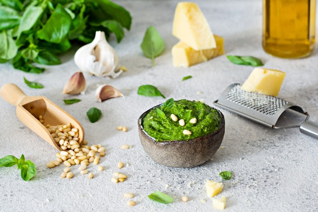 Зеленый соус песто в миске из свежих листьев базилика, кедровых орехов, пармезана, чеснока и оливкового масла на светлом фоне.