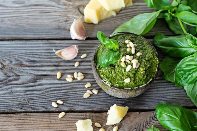 Зеленый песто в миске из свежих листьев базилика, кедровых орехов, пармезана, чеснока и оливкового масла на деревянном фоне