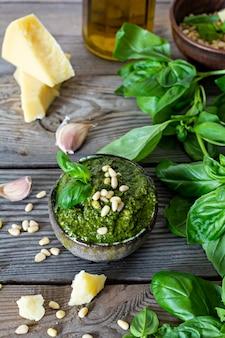 Зеленый песто в миске из свежих листьев базилика