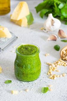 Зеленый соус песто в стеклянной банке из свежих листьев базилика, кедровых орехов, пармезана, чеснока и оливкового масла на светлом фоне.