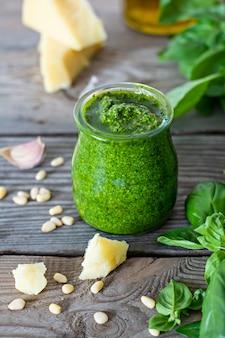 Зеленый соус песто в стеклянной банке из свежих листьев базилика, кедровых орехов, пармезана, чеснока и оливкового масла на деревянном фоне.