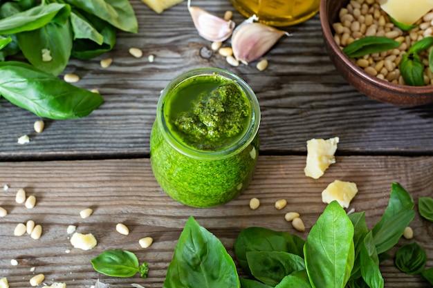 Зеленый песто в стеклянной банке из свежих листьев базилика, кедровых орехов, пармезана, чеснока и оливкового масла на деревянном фоне