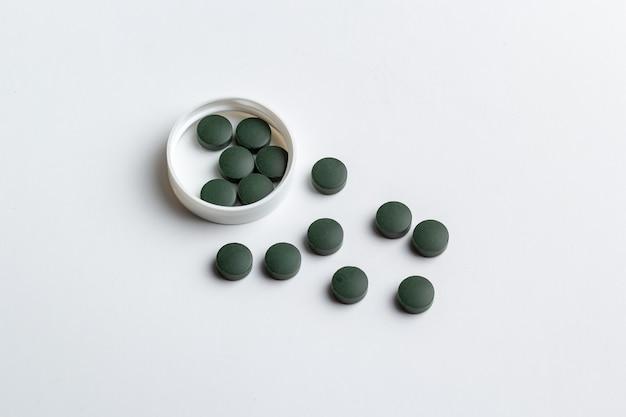 Зеленые таблетки, изолированные на белом фоне