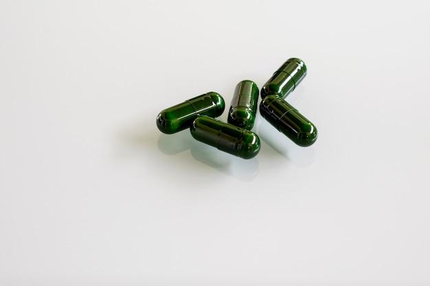 白いガラスのテーブルの上の緑の丸薬