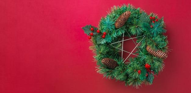 赤い壁に桜の装飾品、星と松のコーンと緑の松葉クリスマスの花輪