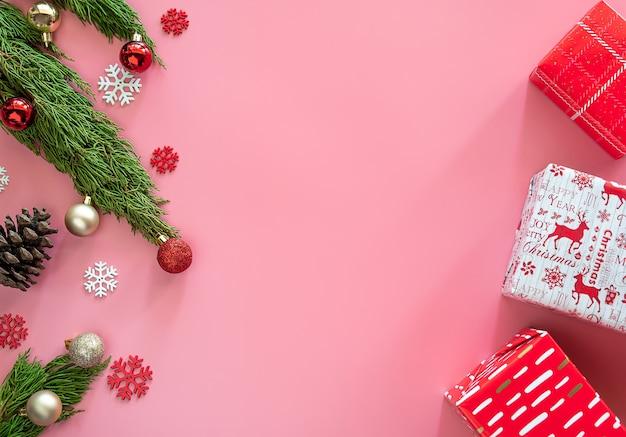 Зеленая сосна, шишка, снежинки, рождественские украшения и подарочная коробка в красной оберточной бумаге на розовом фоне с копией пространства