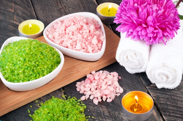 Green and pink sea salt, towel, scented candles and flowers for spa treatments on old wooden background
