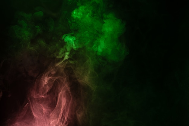 Green and pink steam on a black surface. copy space.