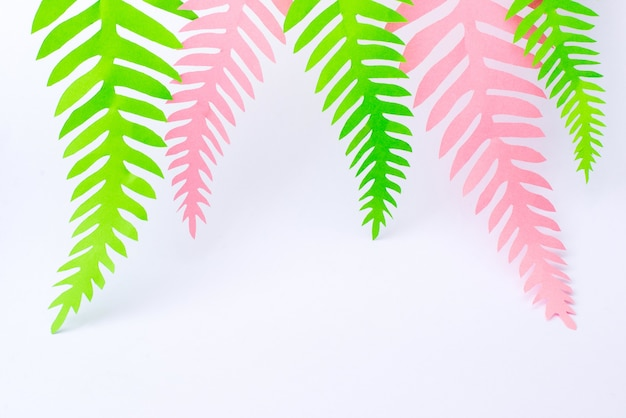 Green and pink tropical paper palm leaves on white surface