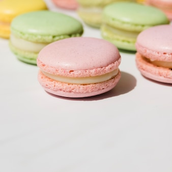 Green and pink whipped cream macaroons on white backdrop