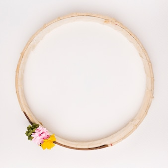 Green; pink and yellow flowers on wooden circular frame against white backdrop