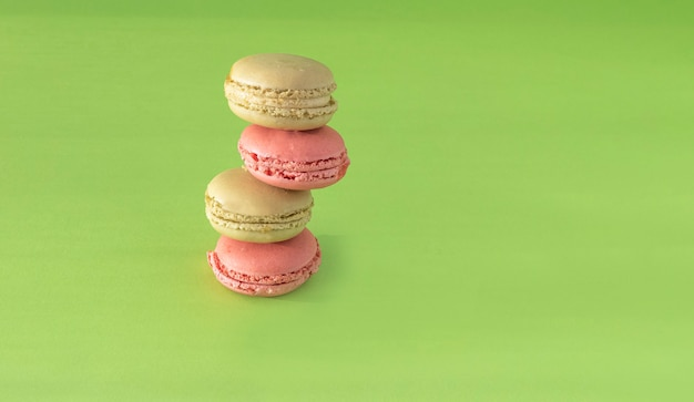 Green pistachio and pink raspberry macaroon cookies arranged in a vertical composition on a green background.