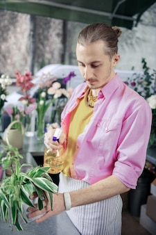 Green plant. concentrated designer wearing colorful uniform while watering green leaves