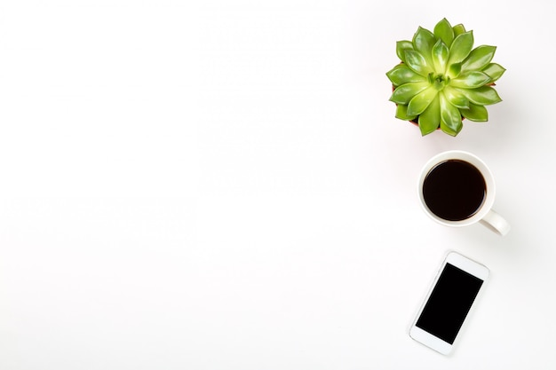 Green plant in a pot, cup of coffee and modern mobile phone on white surface.