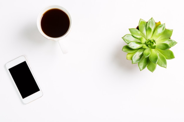 Green plant in a pot with cup of coffee and modern mobile phone and on white table.