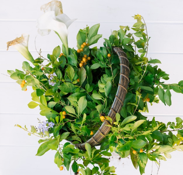 Green plant twigs and flowers in hamper