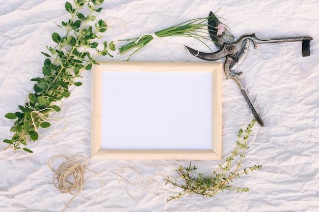 Green plant twigs near garden pruner, photo frame and thread