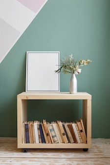 Green plant with a white flower on a bookcase with old books
