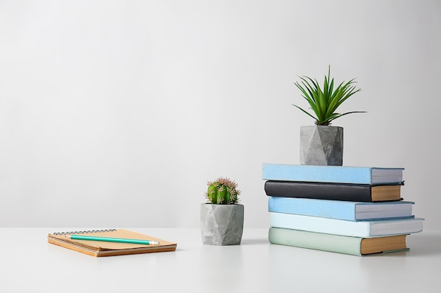 Зеленые растения в горшках с канцелярскими принадлежностями на светлом столе