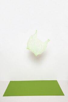 白い背景にぶら下がっている緑のビニール袋
