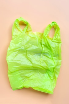 Green plastic bag on yellow background. environment pollution concept.