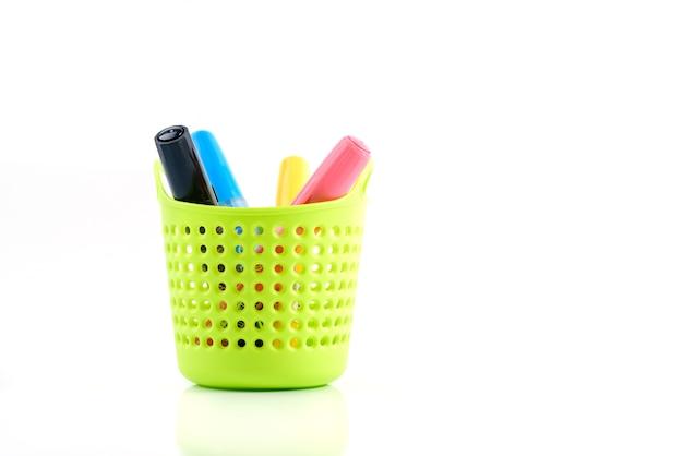 カラフルなペンや文房具を白で隔離される緑のプラスチックバスケット