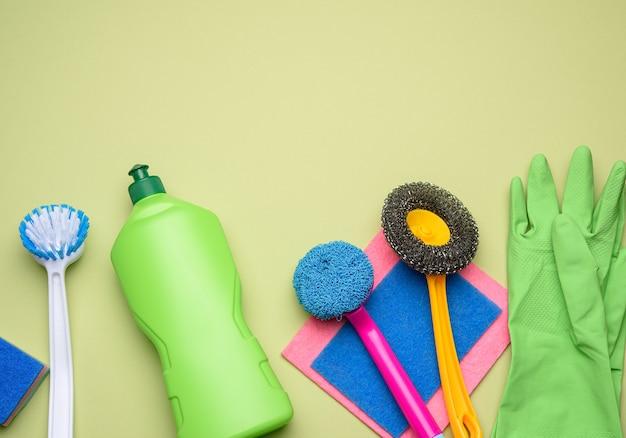 Зеленая пластиковая бутылка и резиновые перчатки для чистки, кисти на зеленом фоне, плоская планировка, набор для чистки
