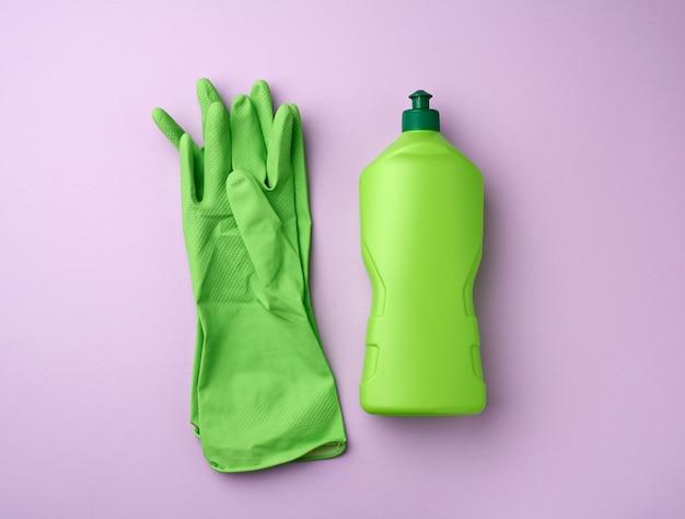 家庭用洗剤とゴム製保護手袋が付いた緑色のプラスチックボトル